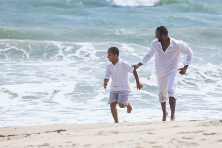 A happy African American family of father and son, man & boy child, running and having fun in the sand and waves of a sunny beach