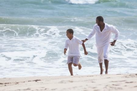 African American: Una familia estadounidense feliz de padre e hijo, hombre y ni�o del muchacho, funcionamiento y divertirse en la arena y las olas de una playa soleada