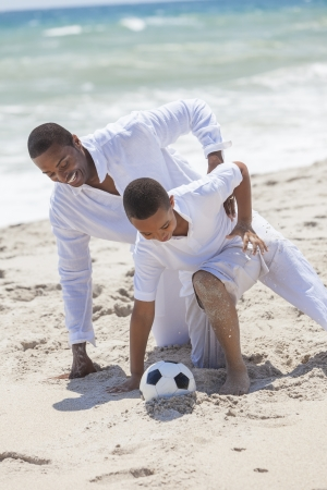 A happy African American family of father and son, man & boy child, having fun playing soccer football in the sand of a sunny beach photo