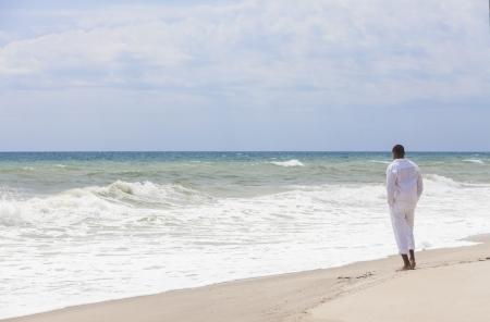 hombre solitario: Hombre afroamericano de pie solo en una playa tropical