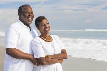 African American: Feliz el hombre rom?ntico senior de afroamericano y joven mujer en una playa tropical desierta