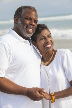 aging american: Happy romantic senior African American man and woman couple holding hands on a deserted tropical beach  Stock Photo
