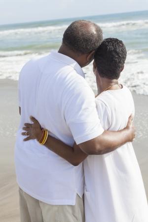 Achteraanzicht van de romantische hoge African American man en vrouw paar op een verlaten tropisch strand