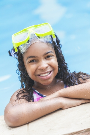 A cute happy young interracial African American girl child relaxing on the side of a swimming pool smiling & wearing pink goggles