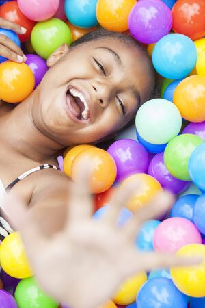 A young African American girl child having fun laughing playing with hundreds of colorful plastic balls Banco de Imagens