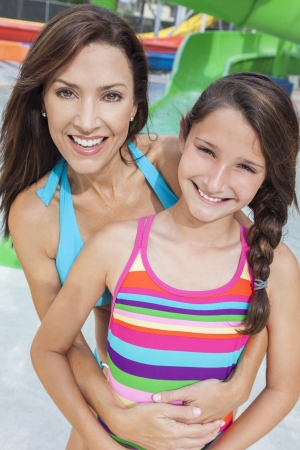 A happy family of mother and daughter, woman and girl child, having fun on vacation at a waterpark