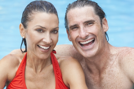 Portrait of a beautiful happy man and woman couple laughing in a swimming pool smiling with perfect teeth. photo
