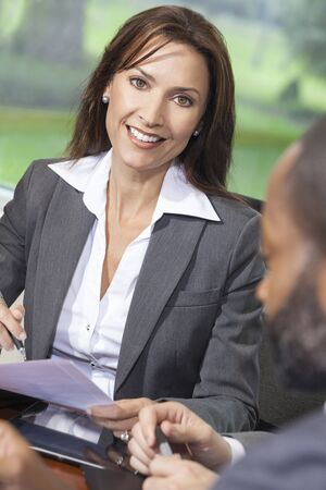 beautiful middle aged woman: Portrait of a beautiful young brunette woman or businesswoman in office meeting
