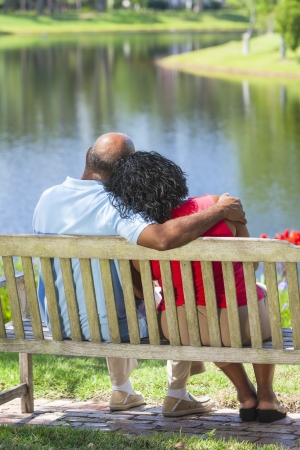 Rear view of a happy romantic senior African American couple sitting on a park bench embracing looking at a lake or river photo