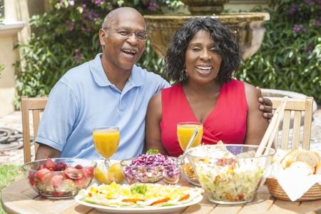 pareja comiendo: Un, hombre sonriente y feliz mujer senior pareja estadounidense comer alimentos saludables en una mesa de picnic al aire libre