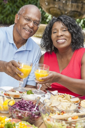 A happy, smiling man and woman senior African American couple drinking orange juice & eating healthy food at a picnic table outside photo
