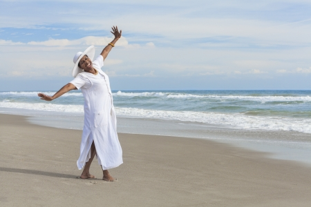 african american: Happy senior African American woman dancing alone on a deserted tropical beach