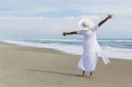 Gelukkig senior Afro-Amerikaanse vrouw dansen alleen op een verlaten tropisch strand