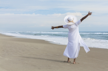 active holiday: Happy senior African American woman dancing alone on a deserted tropical beach