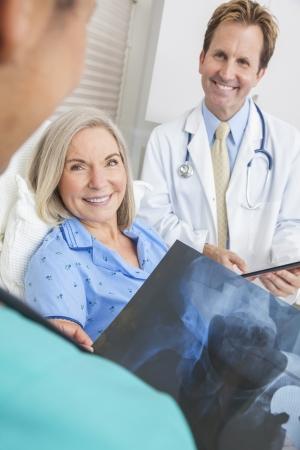 enfermera con paciente: Feliz mujer senior paciente se recuperaba en cama de hospital con el doctor y enfermera mirando reemplazo de cadera de rayos x