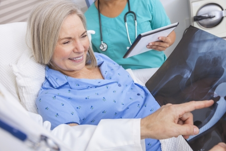 Happy senior woman patient recovering in hospital bed with male doctor and female nurse looking at hip replacement x-ray photo
