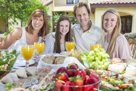 An attractive happy, smiling family of mother, father and two daughters eating healthy food at a table outside. Stock Photo - 19505465