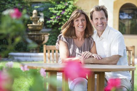 togther: Attractive, romantic and happy middle aged man and woman couple in their forties, sitting togther outside in a garden with flowers