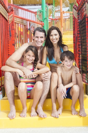 A happy family of mother, father and children, son and daughter, having fun on vacation at a waterpark photo