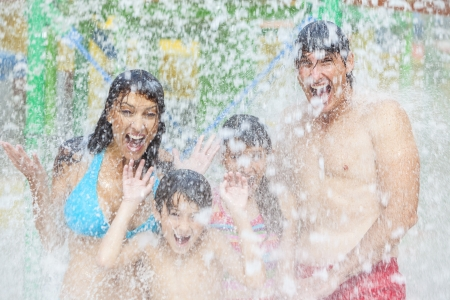 standing water: A happy family of mother, father and children, son and daughter, having fun on vacation at a water park Stock Photo