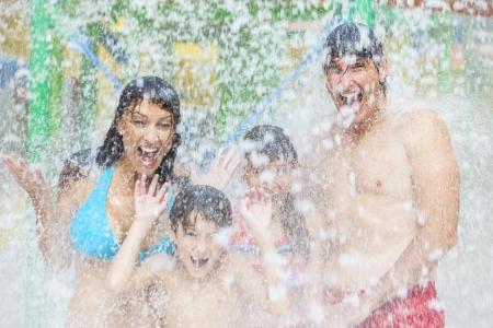 Een gelukkige familie van moeder, vader en kinderen, zoon en dochter, plezier op vakantie in een waterpark Stockfoto