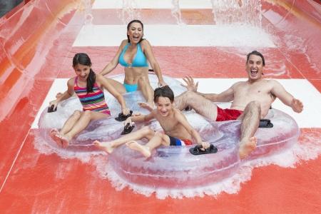 ni�os jugando parque: Una familia feliz de madre, padre e hijos, hijo e hija se divierten en vacaciones en una diapositiva en un parque acu�tico