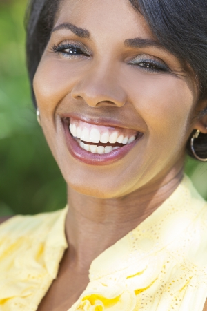 A beautiful happy middle aged African American woman with perfect teeth relaxing and smiling outside Banco de Imagens