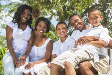 padres e hijos felices: Una familia afroamericano negro feliz de dos padres y tres hijos, dos niños, una niña sentados juntos fuera.