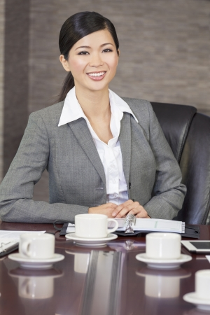 Portrait of a beautiful young Asian Chinese woman or businesswoman in smart business suit sat in an office or boardroom photo