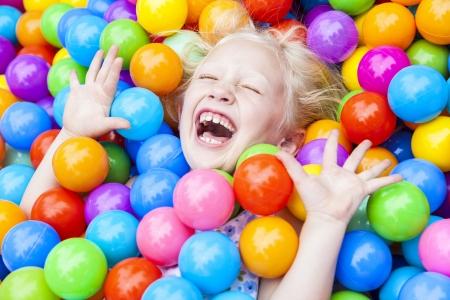 ni�as jugando: Una joven ni�a rubia que se divierten riendo jugando con cientos de pelotas de pl�stico de colores