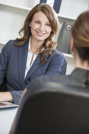 Beautiful young woman or businesswoman in smart business suit sitting at a desk in an office having a meeting photo
