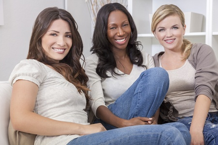 three women: Interracial group of three beautiful young women friends at home sitting together on a sofa smiling and having fun Stock Photo