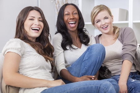 people laughing: Interracial group of three beautiful young women friends at home sitting together on a sofa smiling and having fun Stock Photo