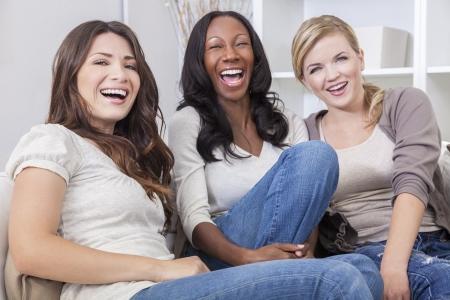 Interraciale groep van drie mooie jonge vrouwen vrienden thuis zitten samen op een bank lacht en plezier