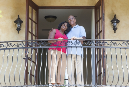 A happy senior African American man and woman couple in their sixties outside together smiling on a hotel or villa balcony