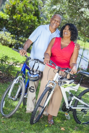 A senior African American woman & man couple riding bicycles in the summer Stock Photo - 19523979