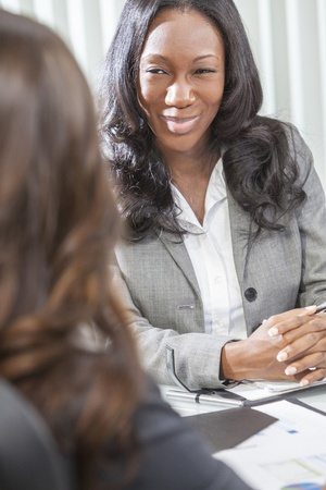 Young black African American woman or businesswoman in smart business suit having a meeting with her colleague photo