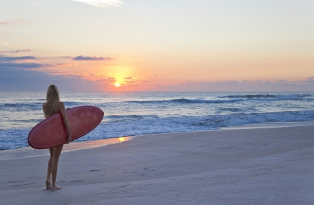 Rear view of three a young women surfer girl in bikinis with red surfboard on beach at sunset or sunrise Stock Photo