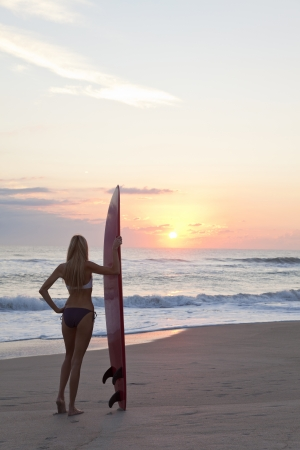 Rear view of a beautiful young woman surfer girl in bikini with surfbord at a beach at sunset or sunrise photo