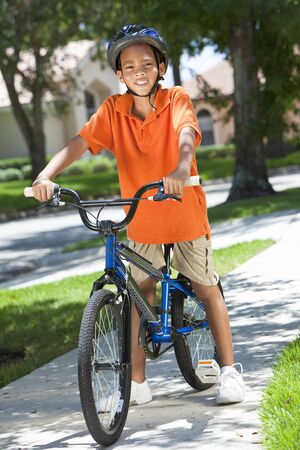 A young African American boy child riding bicycle or bike in the summer Stock Photo - 19524358