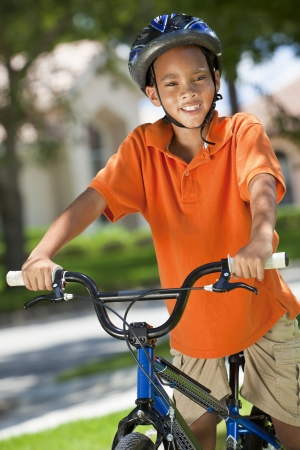 A young African American boy child riding bicycle or bike in the summer Stock Photo - 19524236