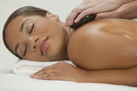 Een Afro-Amerikaanse vrouw die bij een kuuroord, terwijl met een hot stone behandeling of massage