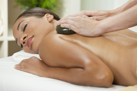 hot stone massage: An African American  woman relaxing at a health spa while having a hot stone treatment or massage Stock Photo