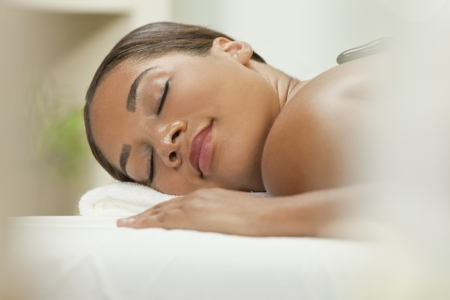 african american woman: An African American  woman relaxing at a health spa while having a hot stone treatment or massage Stock Photo