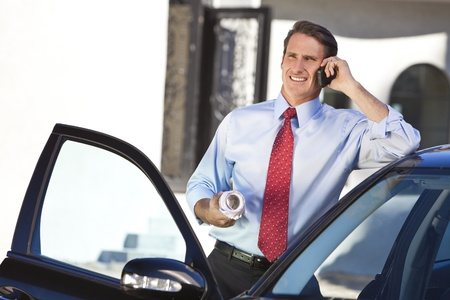 A successful businessman or architect holding plans & talking on his cell phone by a car photo