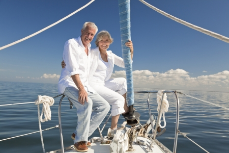 Een gelukkige senior paar zittend op de boeg van een zeilboot op een kalme blauwe zee