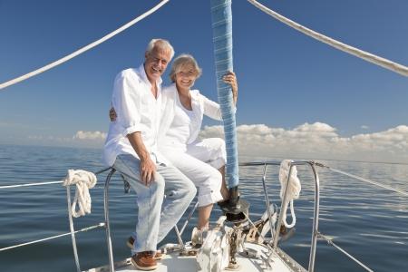 jubilados: Una pareja feliz altos sentado en la proa de un barco de vela en un mar azul en calma
