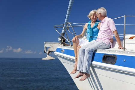 wealthy: A happy senior couple sitting on the deck of a sail boat on a calm blue sea Stock Photo