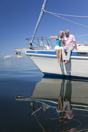 A happy senior couple sitting on the front of a sail boat on a calm blue sea Banco de Imagens