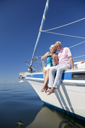 A happy senior couple sitting on the deck of a sail boat on a calm blue sea Banco de Imagens